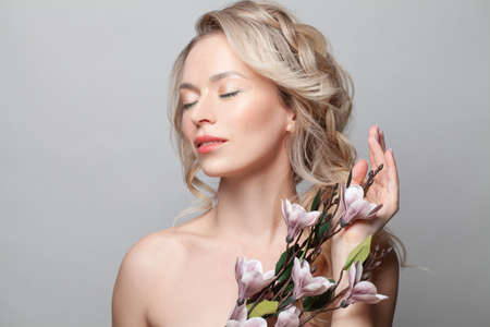 Beauty face. Attractive woman with natural makeup and healthy skin portrait. Beautiful female model holding flowers on gray background. Skin care concept Stockfoto