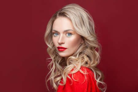 Blonde curly long hair woman with beauty makeup over red background Stockfoto
