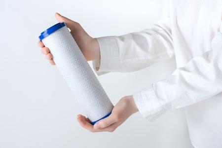cartuccia del filtro dell'acqua in mano umana isolato su bianco Archivio Fotografico