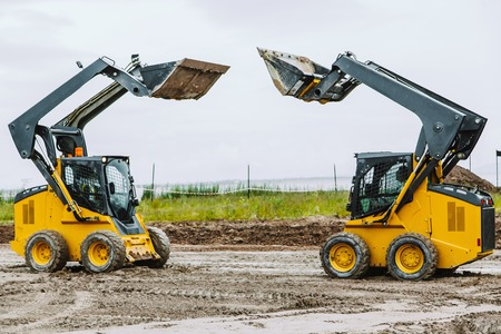 loader: two yellow skid steers with raiced bucket outdoors Stock Photo
