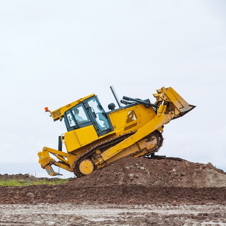 overcome: dirty Yellow bulldozer overcome ground barrier, going up