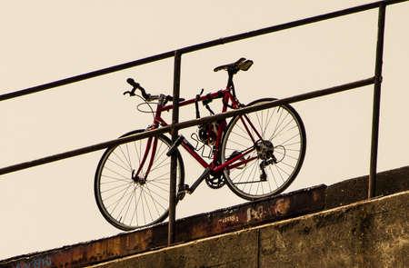 red bicycle locked onto metal railing