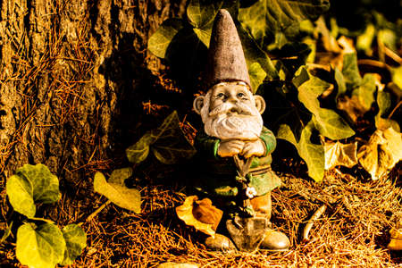 Small garden gnome with shovel in front of tree
