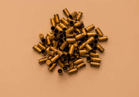 Pile of used bullet cartridges on beige background