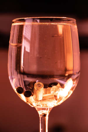 Empty bullet cartridges resting at the bottom of a wine glass like ice cubes