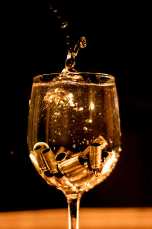 Bullet shells splashing into the bottom of a wine glass like ice cubes