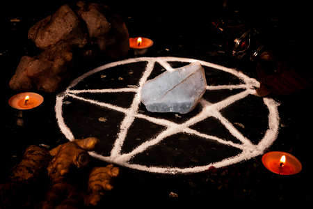 Pentagram made of salt, a symbol used for protection, surrounded by candles, herbs and spices in dim moody lighting.