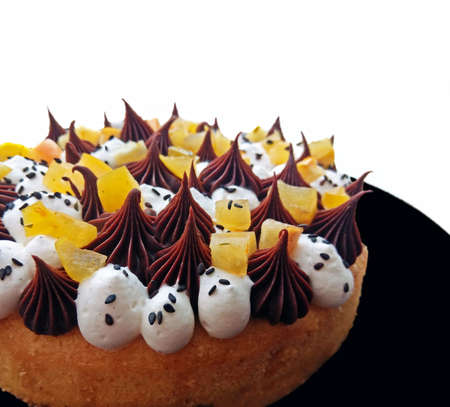 Orange and chocolate sheet cake with whipped cream and black sesame seeds on black and white background