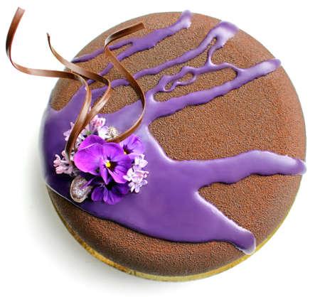 Torta di mousse tonda al cioccolato con fiori primaverili e glassa a specchio vista dall'alto Archivio Fotografico