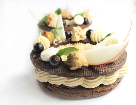 Paris Brest dessert rings with apple slices, black currant berries and meringues on white background
