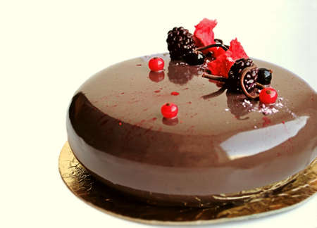 Chocolate cake with shiny mirror glaze, red currants, black currants and blackberries