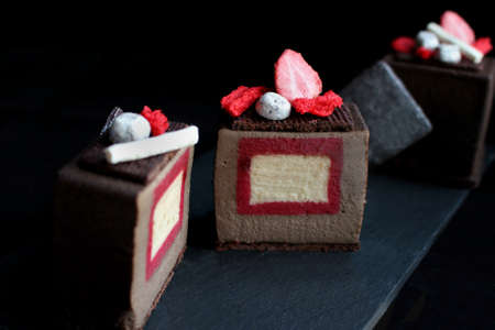 Sliced dark chocolate textured cube dessert with strawberry and vanilla insertion, silver cookie decorations and red sponge on black background