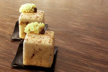 Cappuccino-Würfel-Desserts mit Kaffeebohne und Frühlingsblume auf Holztisch