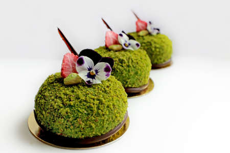 Three green textured pistachio desserts with edible pansy flowers and dried strawberries
