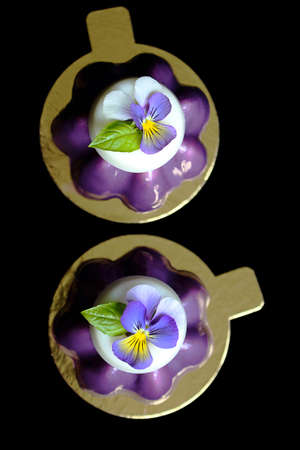 Two purple mousse desserts with white chocolate and pansy flower top view Stok Fotoğraf