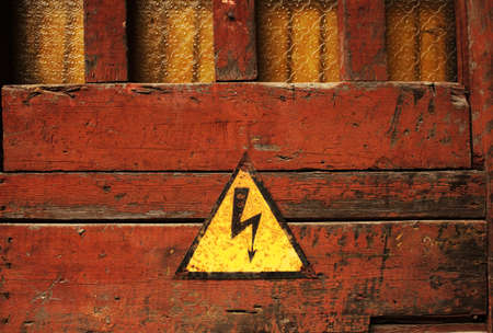 Old rusty black and yellow triangular hazard sign hanfing on brown painted wooden door with yellow glass windows