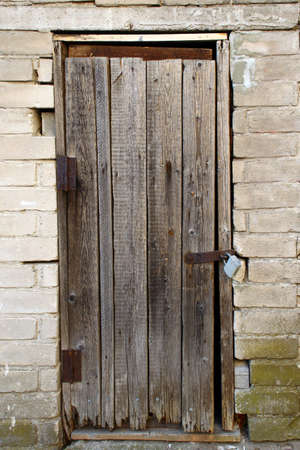 Old wooden door with a lock in white brick wall