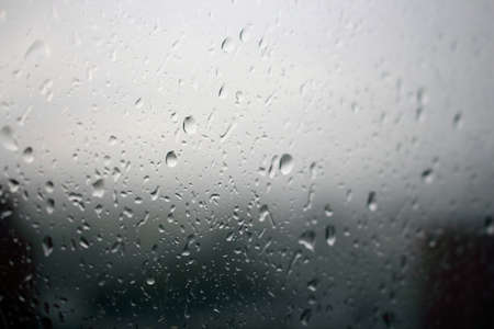 Big raindrops on window glass in stormy weather