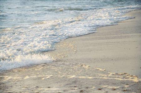 Sea foam waves on sandy seashore background Reklamní fotografie