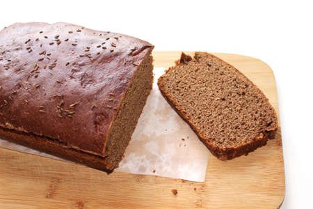 Sliced dark rye hemp seed bread on paper and wooden board on white background