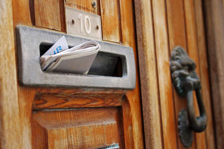Mail box filled with rolled spam newspaper in old door