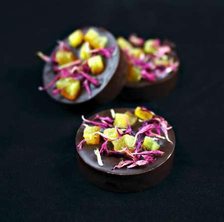 Dark chocolate pralines with orange peel and red knapweed petals isolated on black background Stock Photo