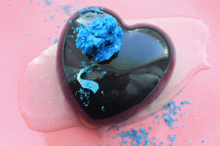 Heart shaped dessert with blue decorations on pink background Banque d'images