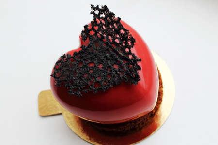 Dessert en forme de coeur rouge avec décoration en dentelle noire sur fond blanc