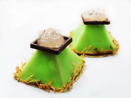 Lime pyramid dessert with aloe vera jelly and flower petals on white background