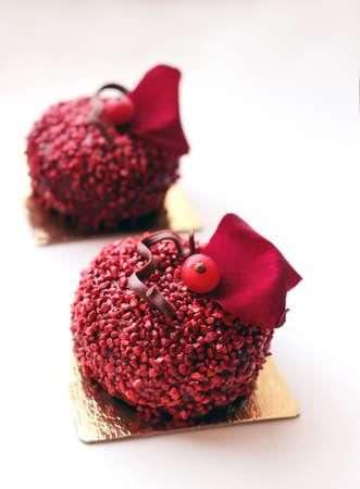 Rote strukturierte Zuckerdesserts mit roter Johannisbeere und rotem Rosenblatt auf weißem Hintergrund