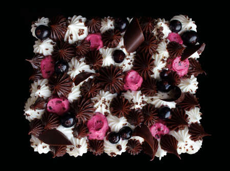 Black currant mousse chocolate sheet cake with whipped cream topping and fresh berries on black background top view