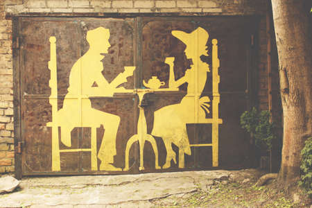 Garage door with man and woman silhouettes drinking tea