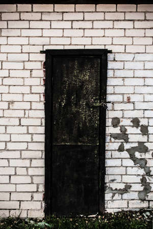 Old spooky dark black wooden door with a lock in white brick wall with spots