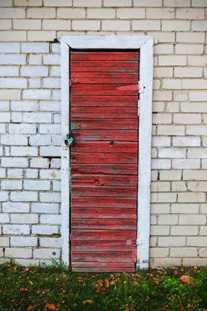 Old red wooden plank door with a lock in white brick wall with green grass bottom
