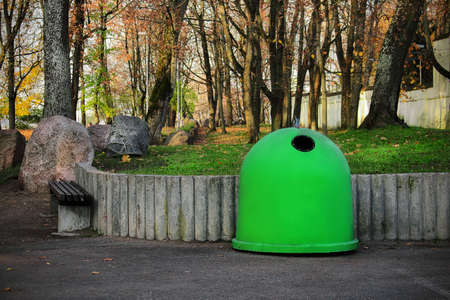 Green garbage containers in park outdoors with bench and big stones on sunny day