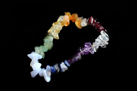 Colorful crystal chakras bracelet isolated on black background Stock Photo