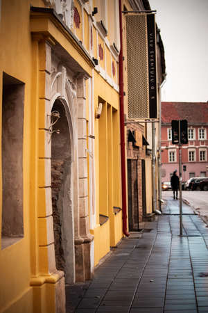Old town Vilnius All Saints wet after rain pavement street with yellow building Stock Photo