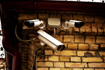 Three white video cameras on yellow brick wall on building corner