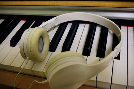 Piano light yellow wood keyboard with white headphones