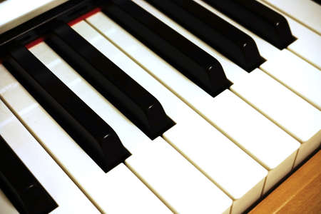 Light yellow wood piano keyboard in bright white light