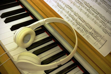 Piano light yellow wood keyboard with white headphones and sheet music