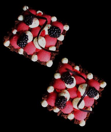 Red currant mousse and blackberry puff pastry desserts with whipped ganache and chocolate spiral decorations