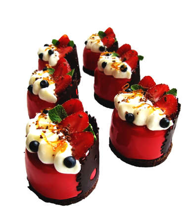 Strawberry mousse desserts with whipped cream, fresh berries and chocolate decorations