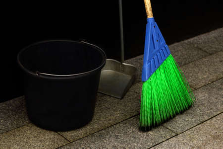 Bright blue and green synthetic street mop with black bucket and a scoop outdoors