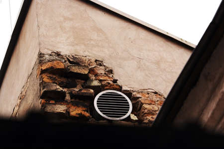 Round ventilation grill in red brick wall with peeled concrete