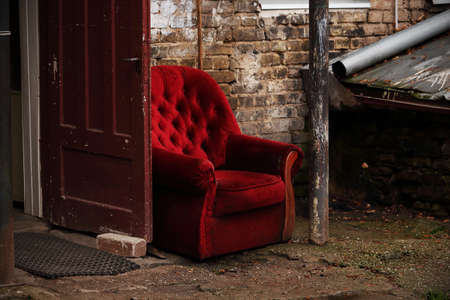 Red velvet armchair standing outdoors outside home with open wooden door Stock Photo