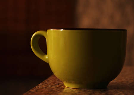 Big green cup standing on table in morning light sepia