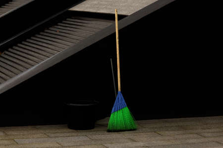 Bright blue and green synthetic street mop with black bucket and a scoop on city square