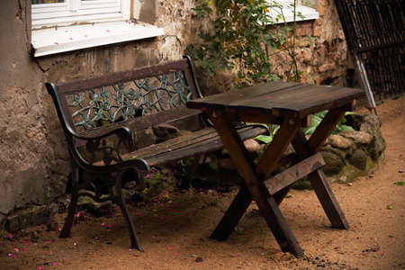 Outdoor patio iron carved bench and table standing outside house Stock Photo