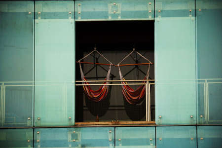 Two red hammocks hanging on modern building balcony